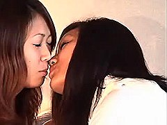 Asian girls taste each other on bed